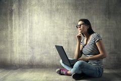 Mujer que usa el ordenador portátil, chica joven en vidrios que piensa en el cuaderno Fotos de archivo libres de regalías