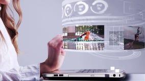Mujer que usa el ordenador portátil con el interfaz del holograma de la aventura del oudoor metrajes