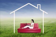 Mujer que usa el ordenador portátil con la imagen de la casa Imagen de archivo
