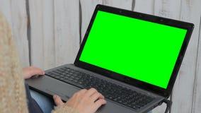 Mujer que usa el ordenador portátil con la pantalla verde almacen de video