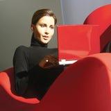 Mujer que usa el ordenador portátil en casa d Imagen de archivo libre de regalías