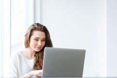 Mujer que usa el ordenador portátil en el país Foto de archivo