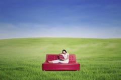 Mujer que usa el ordenador portátil en el sofá en el prado Imagenes de archivo