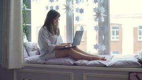 Mujer que usa el ordenador portátil en el travesaño de la ventana metrajes