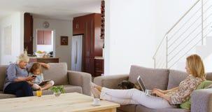 Mujer que usa el ordenador portátil mientras que abuela y nieta que usa el teléfono móvil y la tableta digital almacen de video
