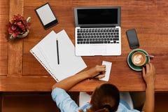 Mujer que usa el ordenador portátil, tomando notas en el café Trabajo Foto de archivo libre de regalías