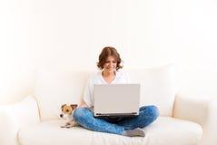 Mujer que usa el ordenador portátil y bebiendo de una taza Imágenes de archivo libres de regalías