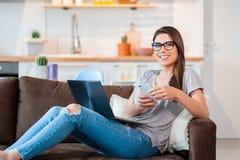 Mujer que usa el ordenador portátil y el teléfono móvil que mienten en el sofá Fotos de archivo