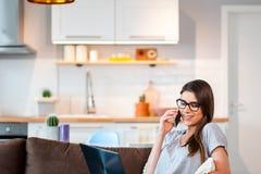 Mujer que usa el ordenador portátil y el teléfono móvil que mienten en el sofá Imagen de archivo