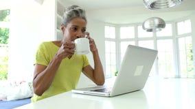 Mujer que usa el ordenador portátil y hablando en el teléfono en cocina en casa metrajes