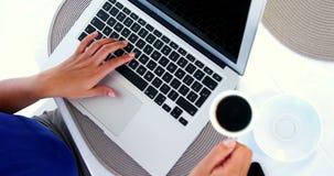 mujer que usa el ordenador portátil y poniendo el café en el suelo metrajes