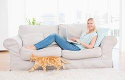 Mujer que usa el ordenador portátil en el sofá mientras que gato que pasa cerca Imagen de archivo
