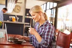 Mujer que usa el ordenador portátil en una cafetería Imágenes de archivo libres de regalías