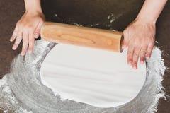 Mujer que usa el rodillo que prepara la formación de hielo real para el adornamiento de la torta Imágenes de archivo libres de regalías