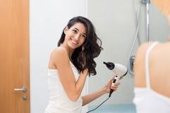 Mujer que usa el secador de pelo imagen de archivo