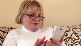 Mujer que usa el smartphone blanco almacen de metraje de vídeo