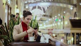 Mujer que usa el smartphone, café de consumición en café almacen de video