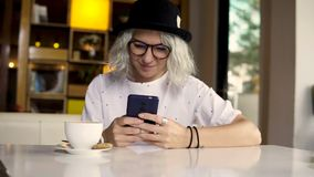 Mujer que usa el smartphone, mandando un SMS en el teléfono móvil metrajes
