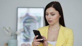 Mujer que usa el smartphone para Internet de la ojeada metrajes