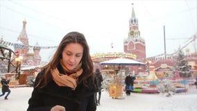Mujer que usa el smartphone que se coloca en el invierno en la Plaza Roja en Moscú, delante del Kremlin y de la catedral de la al almacen de metraje de vídeo