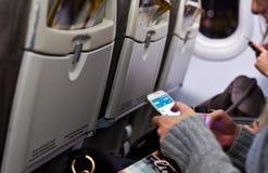 Mujer que usa el smartphone que se sienta en un aeroplano foto de archivo libre de regalías