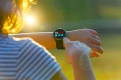 Mujer que usa el smartwatch con su finger fotografía de archivo