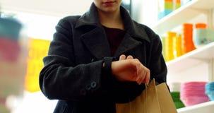Mujer que usa el smartwatch en tienda almacen de metraje de vídeo