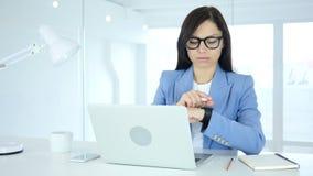 Mujer que usa el smartwatch en el trabajo en oficina almacen de metraje de vídeo