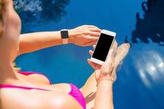 Mujer que usa el smartwatch y el teléfono móvil por la piscina fotos de archivo libres de regalías