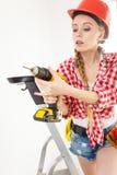 Mujer que usa el taladro en escalera Imagen de archivo