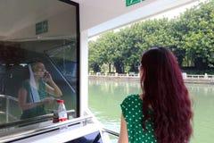Mujer que usa el teléfono celular a bordo Fotos de archivo libres de regalías