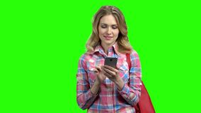 Mujer que usa el teléfono celular en la pantalla verde almacen de metraje de vídeo