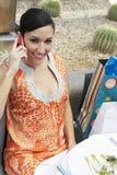Mujer que usa el teléfono celular en un restaurante al aire libre Imagen de archivo