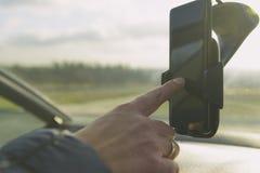Mujer que usa el teléfono del smort mientras que conduce el coche foto de archivo