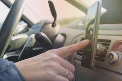 Mujer que usa el teléfono del smort mientras que conduce el coche imagen de archivo