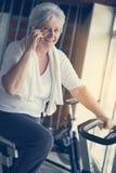 Mujer que usa el teléfono elegante en el gimnasio Mujer que habla en Foto de archivo libre de regalías
