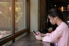 Mujer que usa el teléfono elegante en la tabla, la gente y el concepto de madera de la tecnología fotografía de archivo libre de regalías