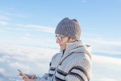 Mujer que usa el teléfono elegante en las montañas Vista panorámica de las montañas coronadas de nieve en la estación fría del in imagenes de archivo