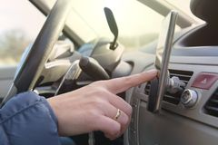 Mujer que usa el teléfono elegante mientras que conduce el coche imagenes de archivo