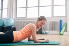 Mujer que usa el teléfono elegante mientras que ejercita en el gimnasio Fotos de archivo libres de regalías