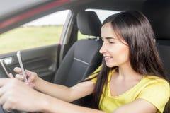Mujer que usa el teléfono en el coche Fotografía de archivo