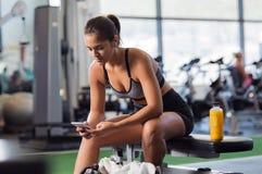 Mujer que usa el teléfono en el gimnasio imagen de archivo