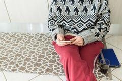 Mujer que usa el teléfono en la sentada interior casera en piso con el vidrio de la tableta y del café Parte del cuerpo solamente imagen de archivo