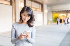 Mujer que usa el teléfono móvil al mensaje de texto Fotos de archivo libres de regalías