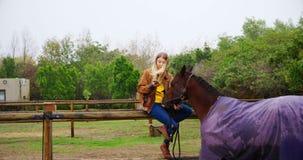 Mujer que usa el teléfono móvil con el caballo en la cerca de madera 4k almacen de metraje de vídeo