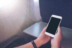 Mujer que usa el teléfono móvil en aeroplano Imágenes de archivo libres de regalías