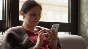 Mujer que usa el teléfono móvil en café almacen de metraje de vídeo