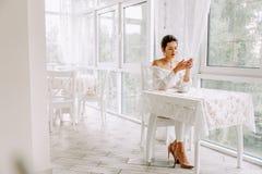 Mujer que usa el teléfono móvil en café Mano femenina con smartphone y café Fotos de archivo libres de regalías