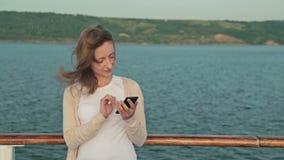 Mujer que usa el teléfono móvil en la cubierta del barco de cruceros