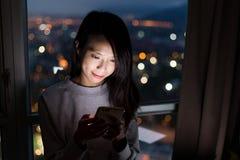 Mujer que usa el teléfono móvil en la noche Fotografía de archivo